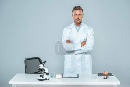Photo for Handsome scientist standing with crossed arms near table isolated on white - Royalty Free Image