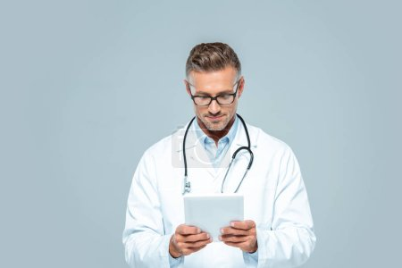 Photo for Handsome doctor with stethoscope looking at tablet isolated on white - Royalty Free Image