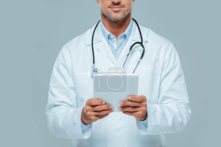 cropped image of doctor in white coat holding tablet isolated on white