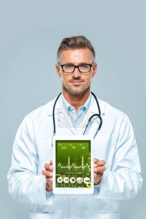 Photo pour Beau médecin avec stéthoscope montrant comprimé avec appareil médical isolé sur blanc - image libre de droit