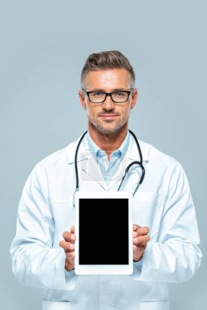 handsome doctor with stethoscope showing tablet with blank screen and looking at camera isolated on white
