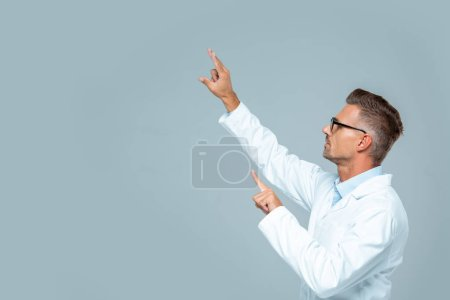 Photo for Side view of handsome scientist in glasses moving something isolated on grey, artificial intelligence concept - Royalty Free Image