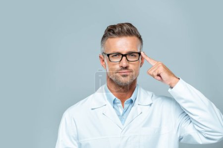 Photo for Handsome scientist in glasses pointing on his head and looking at camera isolated on grey, artificial intelligence concept - Royalty Free Image