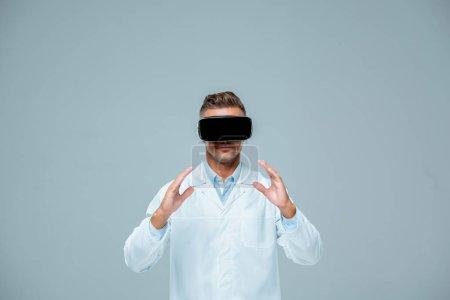 Foto de Científico en tenencia de auriculares de realidad virtual que algo aislado en gris, concepto de inteligencia artificial - Imagen libre de derechos
