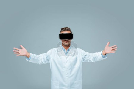 scientist in virtual reality headset holding something in open arms isolated on grey, artificial intelligence concept