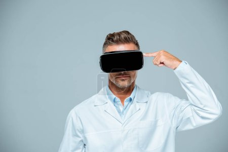 scientist  in virtual reality headset pointing on his head isolated on grey, artificial intelligence concept