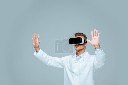scientist in virtual reality headset touching something in air isolated on grey, artificial intelligence concept