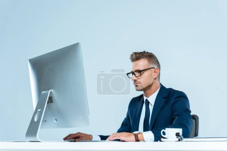 handsome businessman in suit and glasses looking at computer at table isolated on white