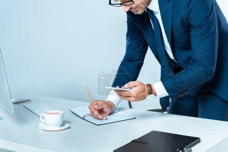 Photo pour Image recadrée de l'homme d'affaires en regardant smartphone et en écrivant quelque chose isolé sur blanc - image libre de droit