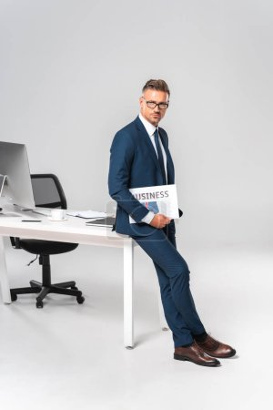 Photo for Handsome businessman holding newspaper, leaning on table and looking at camera isolated on white - Royalty Free Image