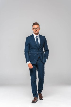 Photo for Handsome businessman in suit and glasses walking and looking at camera isolated on white - Royalty Free Image