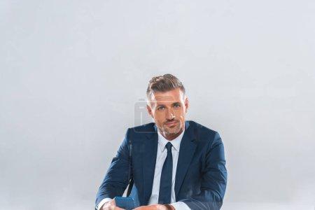 Photo pour Bel homme d'affaires tenant smartphone et regardant loin isolé sur blanc - image libre de droit