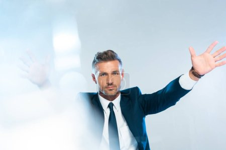 handsome businessman holding something and looking at camera isolated on white, artificial intelligence concept