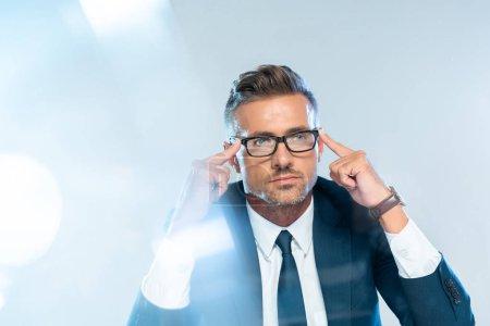 Photo pour Bel homme d'affaires en lunettes touchant la tête isolé sur blanc, concept d'intelligence artificielle - image libre de droit