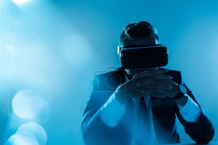Photo for Businessman in virtual reality headset sitting isolated on blue, artificial intelligence concept - Royalty Free Image
