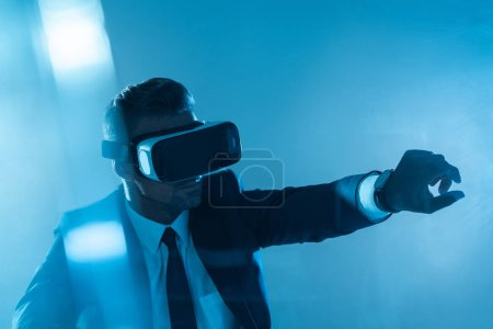 businessman in virtual reality headset touching something isolated on blue, artificial intelligence concept