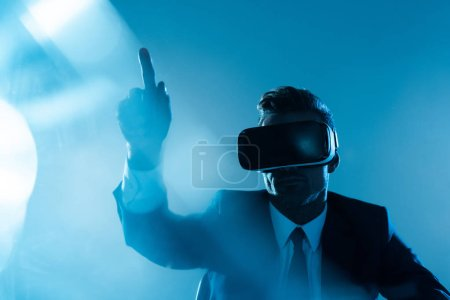 businessman in virtual reality headset pointing on something isolated on blue, artificial intelligence concept