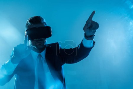 Photo for Businessman in suit and virtual reality headset touching something isolated on blue, artificial intelligence concept - Royalty Free Image