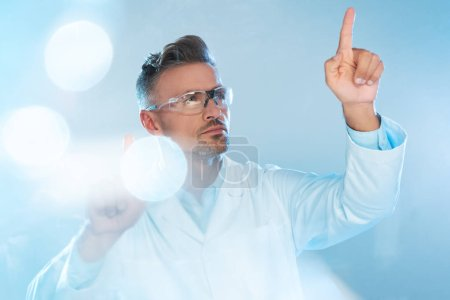 Photo for Handsome technologist in protective glasses and white coat touching something isolated on white, artificial intelligence concept - Royalty Free Image