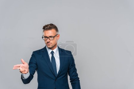 handsome businessman in glasses pointing on something isolated on grey, artificial intelligence concept