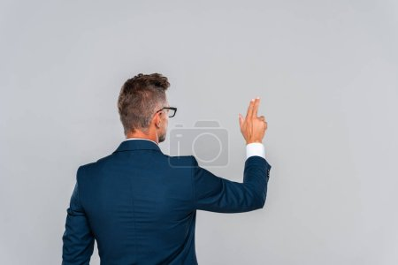 Photo for Back view of businessman in glasses touching something isolated on grey, artificial intelligence concept - Royalty Free Image