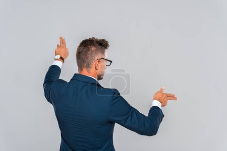 rear view of businessman in glasses touching something isolated on grey, artificial intelligence concept