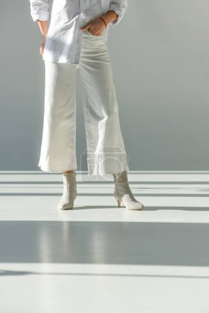 Photo for Cropped image of woman in fashionable trousers and shoes standing on white - Royalty Free Image