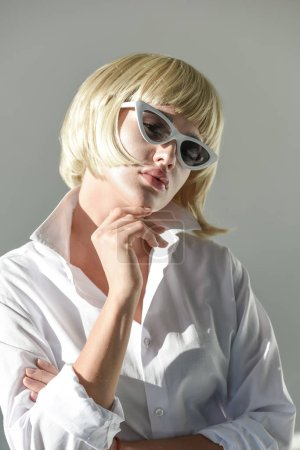 Photo for Portrait of attractive blonde woman in sunglasses and fashionable white outfit looking at camera isolated on white - Royalty Free Image