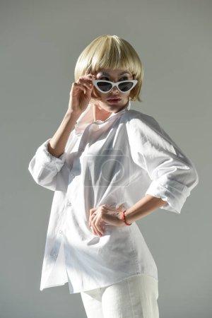 Photo pour Jolie femme blonde en tenue blanche à la mode, regardant au-dessus des lunettes de soleil isolés sur blanc - image libre de droit