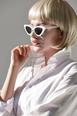 portrait of attractive blonde woman in sunglasses and fashionable shirt isolated on white