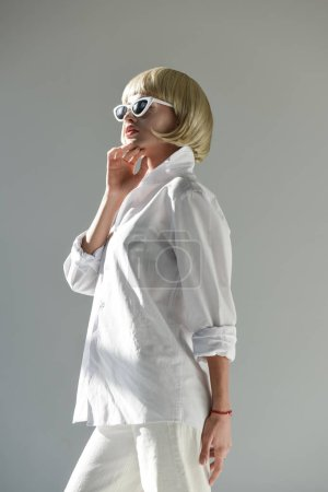 low angle view of attractive blonde woman in sunglasses and fashionable white outfit looking away isolated on white