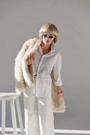 Photo pour Jolie femme blonde en lunettes de soleil et tenue d'hiver à la mode avec manteau en fausse fourrure sur blanc - image libre de droit