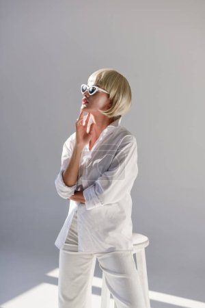 attractive blonde woman in sunglasses and fashionable white outfit on white