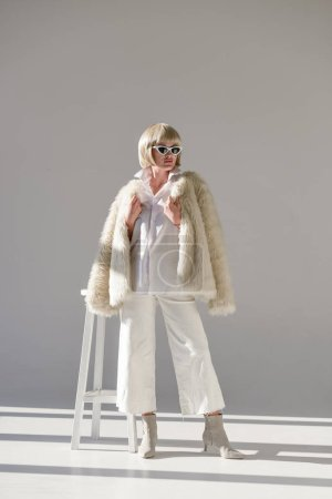 beautiful blonde girl in sunglasses and fashionable winter outfit with faux fur coat standing on white