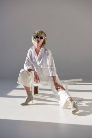 attractive blonde woman in sunglasses and fashionable white outfit sitting on chair on white