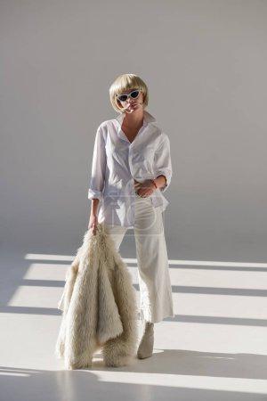Photo pour Jolie femme blonde à lunettes de soleil et de la tenue d'hiver à la mode posant avec manteau de fourrure blanc - image libre de droit