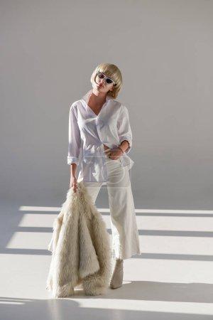 Photo pour Belle femme blonde à lunettes de soleil et de la tenue d'hiver élégant posant avec manteau de fourrure blanc - image libre de droit