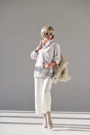 Photo pour Shooting de mode de la jolie femme blonde debout dans les lunettes de soleil et de la tenue d'hiver élégant avec manteau de fourrure blanc - image libre de droit