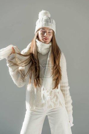 Photo pour Jolie femme en pull en hiver à la mode et écharpe debout les yeux fermés isolé sur blanc - image libre de droit