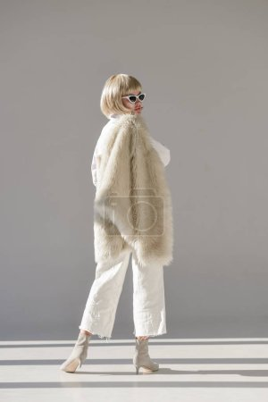 back view of attractive blonde woman in sunglasses and fashionable winter outfit standing with faux fur coat on white