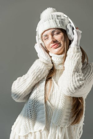 happy attractive woman in fashionable winter sweater and scarf listening music with headphones isolated on grey