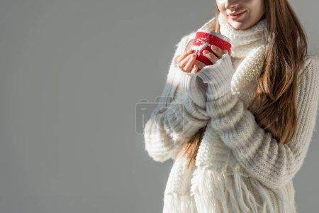 Photo pour Image recadrée de la femme en pull d'hiver à la mode et écharpe tenant tasse de thé isolé sur gris - image libre de droit