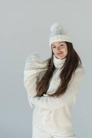 Photo pour Heureuse femme attirante en pull en hiver à la mode et écharpe en regardant caméra isolé sur blanc - image libre de droit