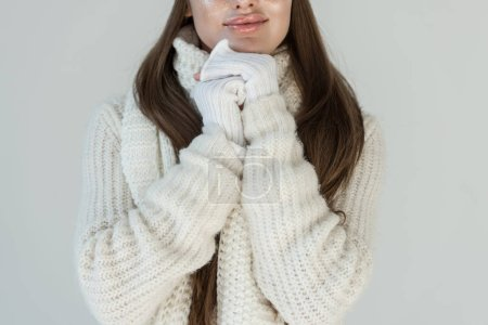 cropped image of woman in fashionable winter sweater and scarf isolated on white