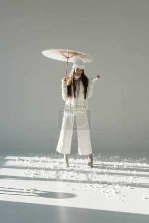 attractive woman in fashionable winter sweater and scarf standing with paper umbrella on white