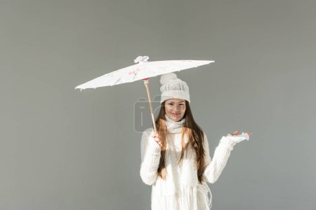 attractive woman in fashionable winter sweater and scarf standing under paper umbrella isolated on grey