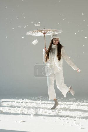 attractive woman in fashionable winter sweater and scarf jumping under paper umbrella, snow falling on white