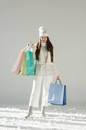 Photo pour Jolie femme pull en hiver à la mode et écharpe debout avec des sacs à provisions et regardant la caméra sur blanc - image libre de droit