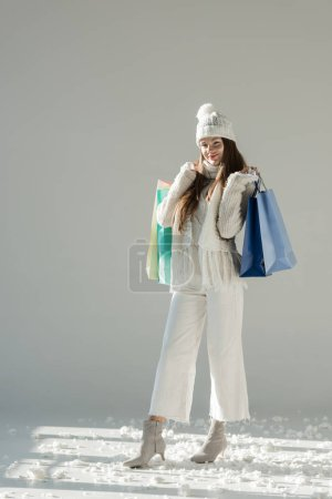cheerful attractive woman in stylish winter sweater and scarf standing with shopping bags on white