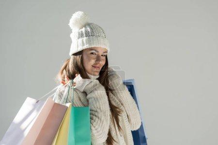 Photo pour Portrait de la belle femme pull en hiver à la mode et écharpe debout avec des sacs à provisions isolés sur blanc - image libre de droit